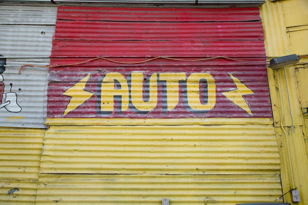 Painting on corrugated metal reflects a sign painter's steady hand at the Cesar Chavez Body Shop, 1400 Cesar E. Chavez Avenue in East Los Angeles.