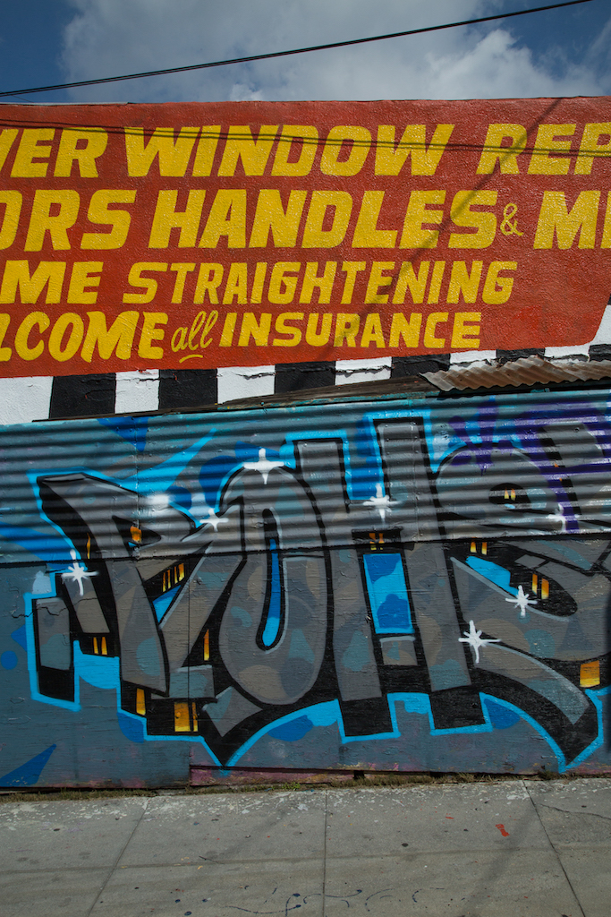 Some sign painters start as taggers. Here, an example of the work of both stand side by side at Cesar Chavez Body Shop, 1400 Cesar E. Chavez Avenue in East Los Angeles.