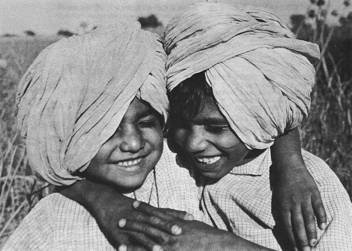 Gurmel's two little boys, Ranjit and Surindar, sat hunched and laughing on the bank