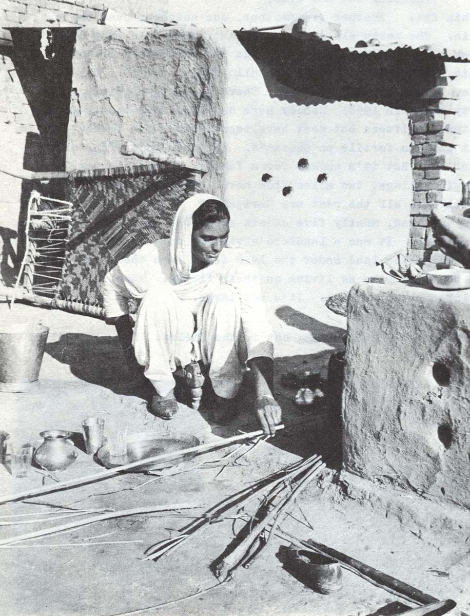 SURGIT sits on a low stool before the outdoor hearth, preparing the evening meal