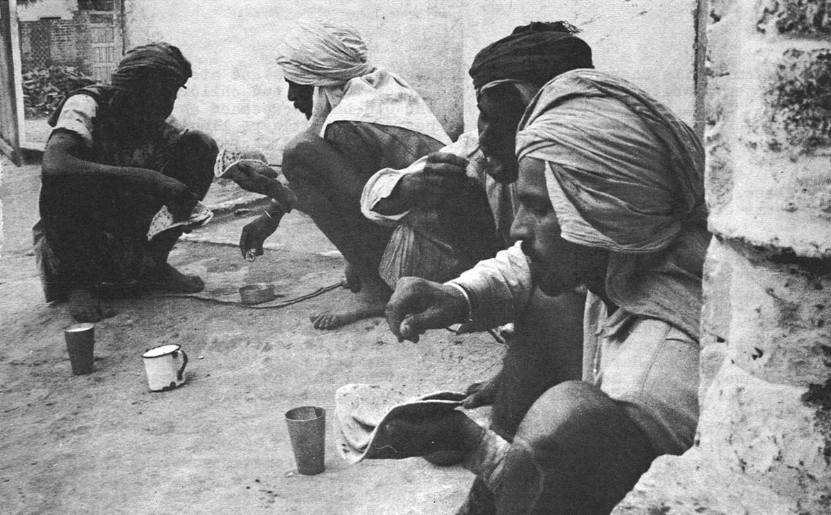 At lunch, the Harijans squatted on the ground in Charan's courtyard