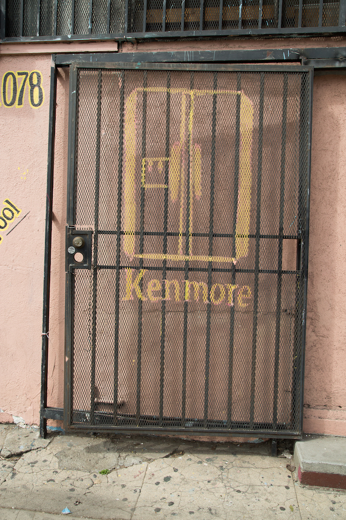 Behind a metal security door at La Segunda De Paco at 3223 S. Central Avenue, a drawing of a Kenmore refrigerator. Yellow letters advertising other appliance brands adorn the pink exterior.