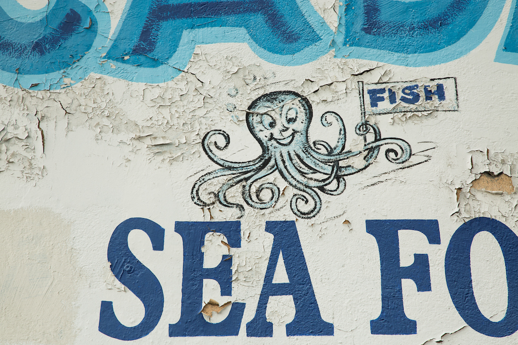 "A smiling octopus holds a sign hawking ""FISH"" at Pescaderia, 5407 S. Central Avenue."