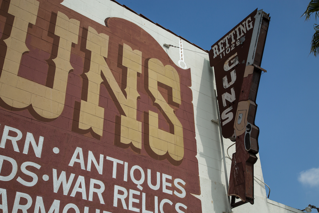 In Culver City, at 11029 Washington Boulevard, Martin B. Retting has a rifle painted on the side of the building, as well as fashioned on a blade sign. A large hand lettered sign advertises modern and antique guns, swords, war relics and armor.