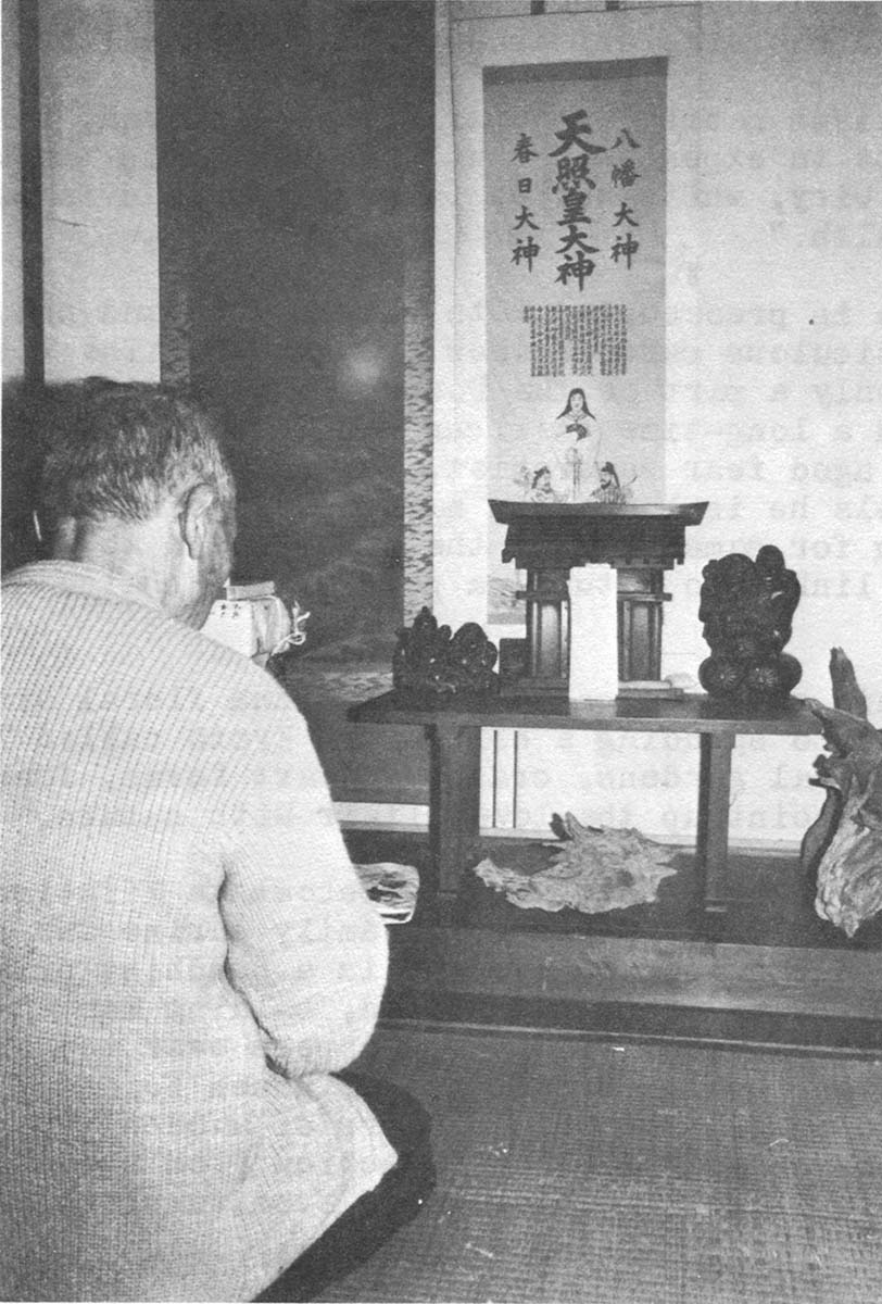 "Mr. Hoso at his family shrine decorated with driftwood ""sculpture."""